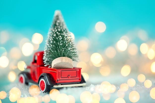 Rotes spielzeugauto mit einem weihnachtsbaum auf dem dach auf einem festlichen blauen hintergrund des bokehs. weihnachts- und neujahrskonzept