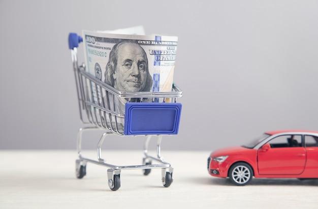 Rotes spielzeugauto und geld im warenkorb. kaufe auto