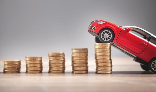 Rotes spielzeugauto und münzen auf dem schreibtisch.