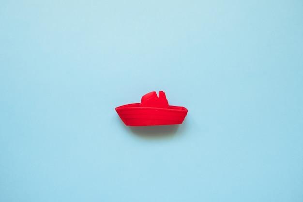 Rotes spielzeugboot auf blauem seekopienraum. strandurlaub konzept