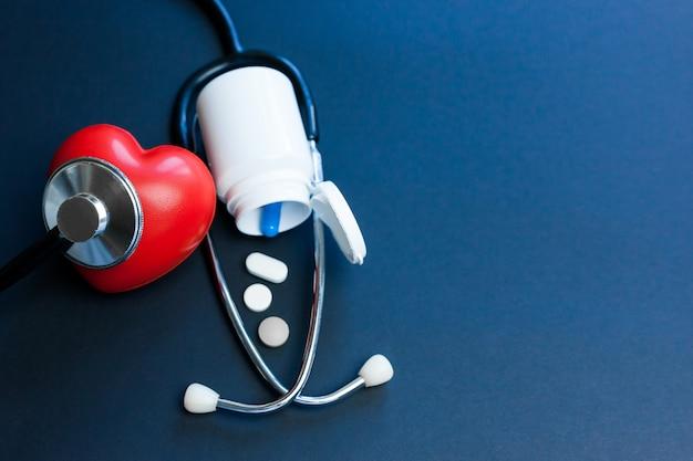Rotes spielzeugherz und stethoskop, die auf dunklem hintergrund liegen