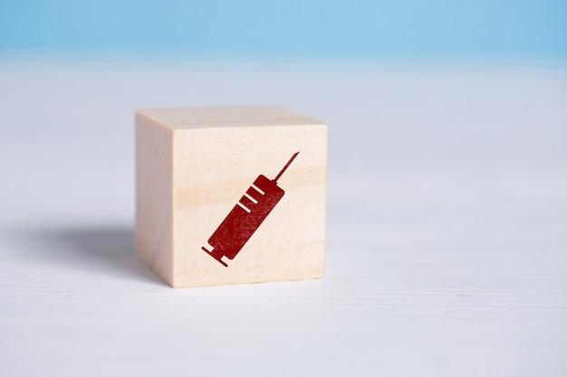 Rotes spritzenzeichen auf einem holzwürfel.