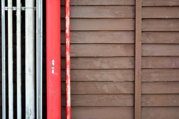Rotes stahlrohr am antiken hölzernen gebäude