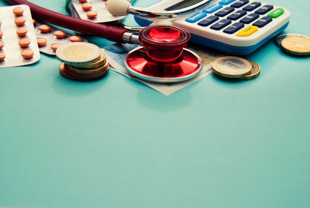 Rotes stethoskop auf einem stapel von münzen, pillen über blau. copyspace. medizin und gesundheitswesen.