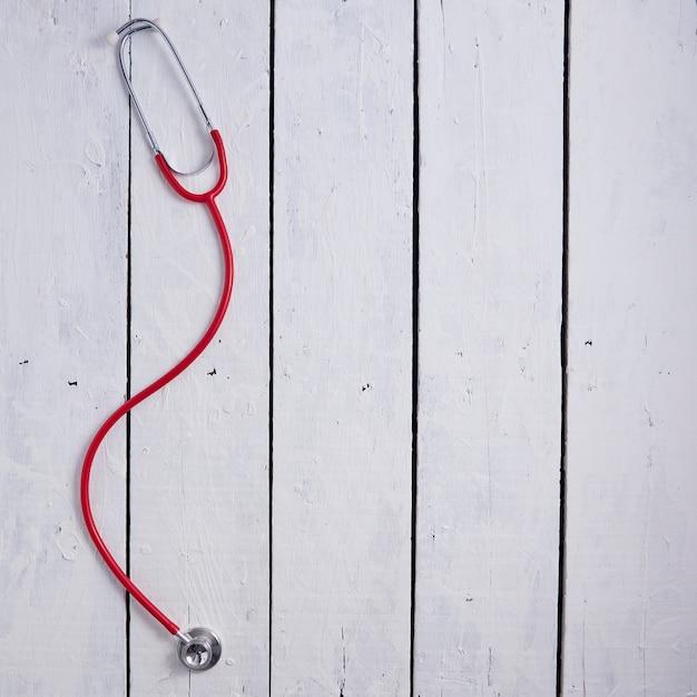 Rotes stethoskop auf weißem tisch