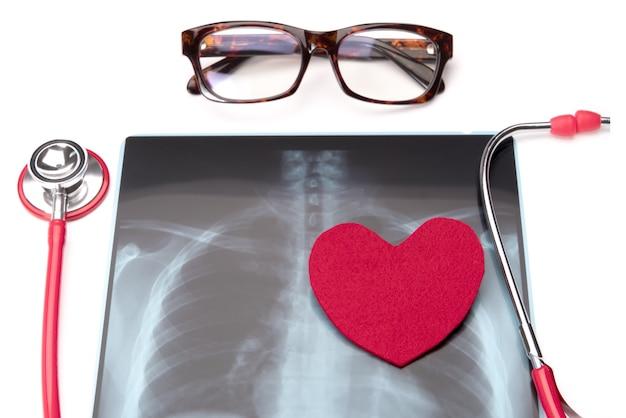 Rotes stethoskop des gesundheitswesens und der medizin und rotes herzsymbol auf röntgenstrahlfilm