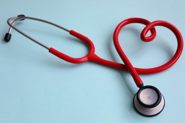 Rotes stethoskop mit herzen auf blauem modernem hintergrund