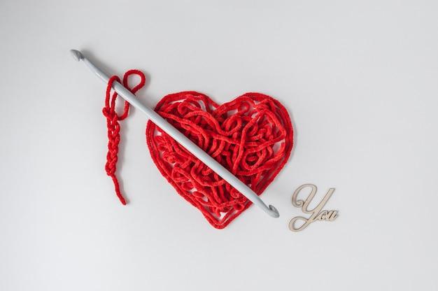Rotes strickgarn mit häkelnadel und holzschild sie. liebeserklärung: ich liebe dich. valentinstag minimales konzept.