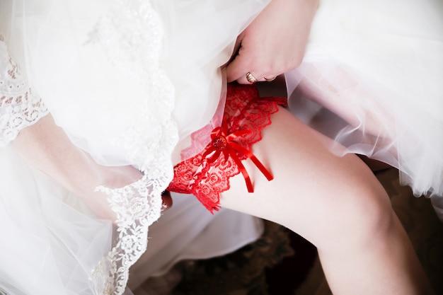 Rotes strumpfband am bein der braut, morgenbraut, die braut trägt ein strumpfband am bein