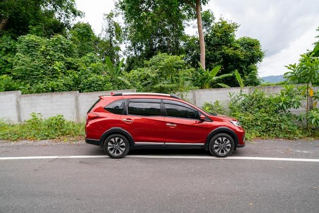 Rotes suv-auto auf asphaltstraße mit gebirgsgrünwaldtransport, zum des konzeptes zu reisen