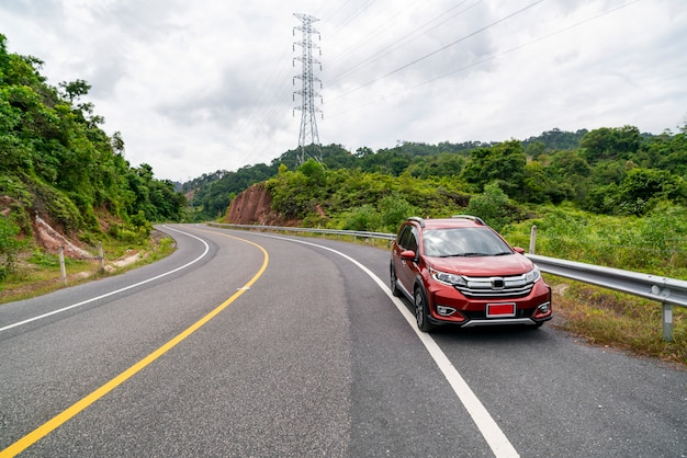 Rotes suv-auto auf asphaltstraße mit gebirgsgrünwaldtransport