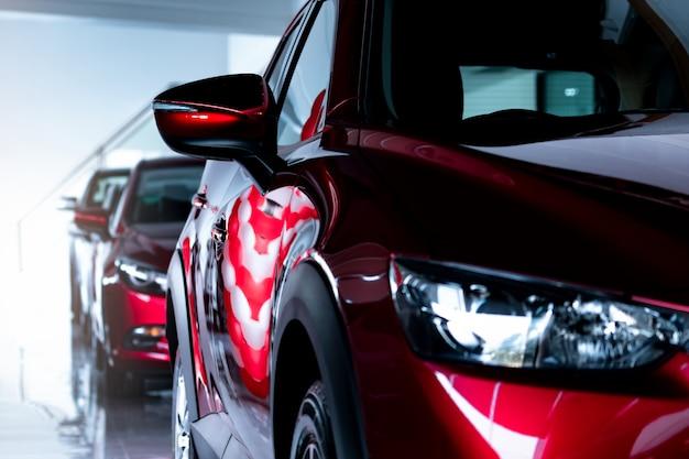 Rotes suv-auto im modernen ausstellungsraum geparkt. neues und luxuriöses suv-kompaktauto. autohauskonzept. automobilindustrie. autoleasinggeschäft. vorderansicht des roten glänzenden autos, das im ausstellungsraum geparkt wird.