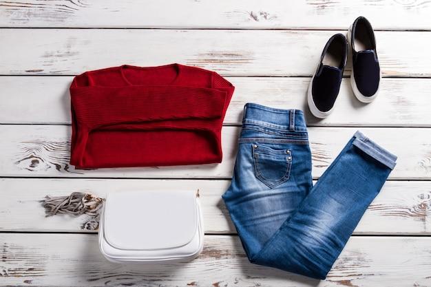 Rotes sweatshirt und jeans der dame. weibliche kleidung auf hölzernem hintergrund. auswahl an frühlings-freizeitkleidung. neue kollektion im outlet-shop.