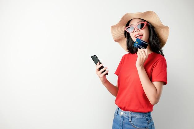 Rotes t-shirt der asiatin des lächelns glücklich, das den smartphone und kreditkarte online kaufen hält.