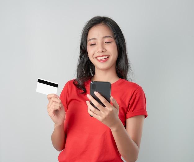 Rotes t-shirt der asiatin des lächelns glücklich, das den smartphone und kreditkarte online kaufen hält