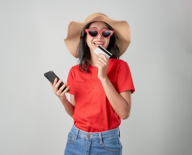 Rotes t-shirt der asiatin des lächelns glücklich, welches den smartphone und kreditkarte online kaufen auf grau hält.