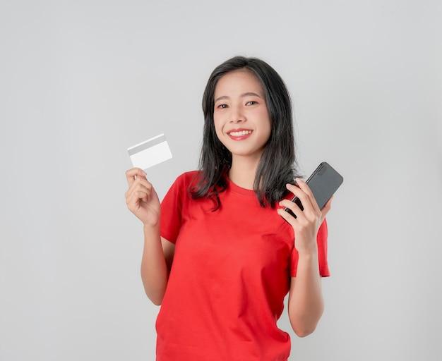Rotes t-shirt der asiatin des lächelns glücklich, welches den smartphone und kreditkarte online kaufen auf grauem hintergrund hält.
