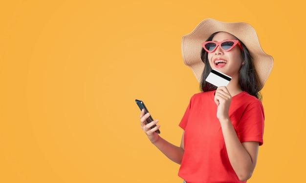 Rotes t-shirt der asiatin des lächelns glücklich, welches den smartphone und kreditkarte online kaufen auf orange hält.