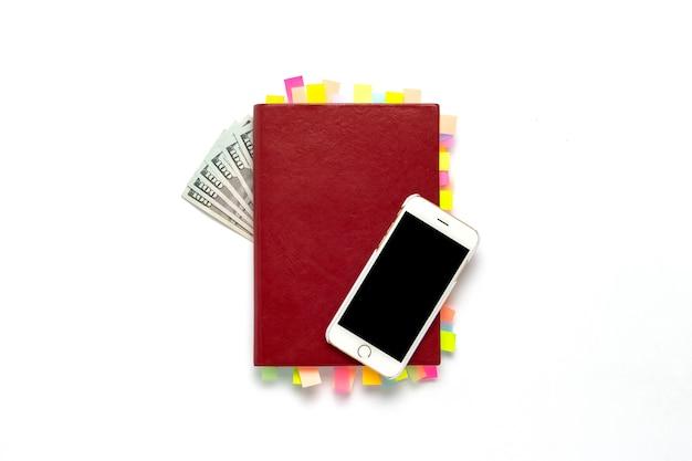 Rotes tagebuch mit aufklebern auf den seiten, weißes telefon, hundert-dollar-scheine, weißer hintergrund. konzept eines erfolgreichen geschäfts, viele meetings und pläne für einen langen zeitraum. flache lage, draufsicht