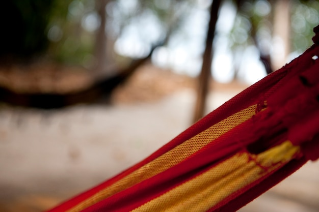 Rotes und gelbes gestreiftes hängemattendetail mit unfocused hängematte im hintergrund