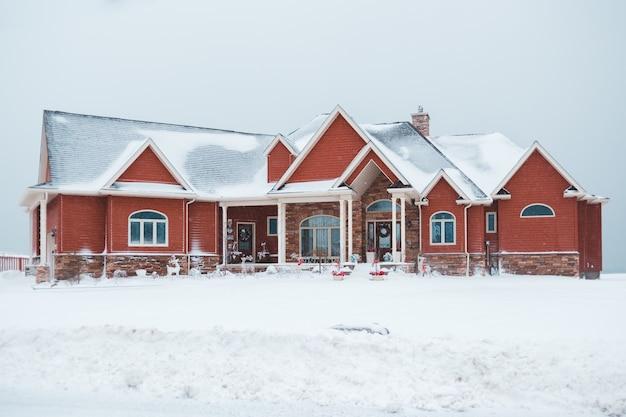 Rotes und graues haus während des schnees
