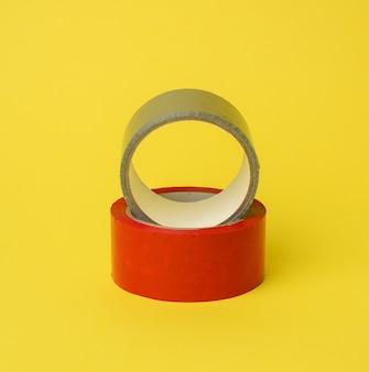 Rotes und graues klebeband lokalisiert auf gelbem hintergrund, nahaufnahme