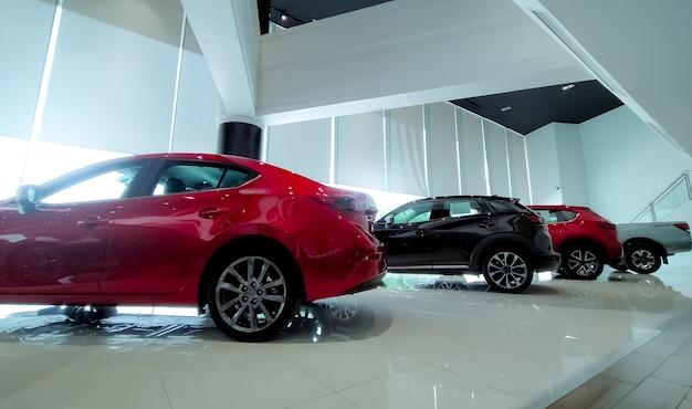 Rotes und schwarzes auto im modernen ausstellungsraum geparkt. autohaus und autoleasing-konzept. automobilindustrie. moderner luxus-showroom. neues auto im ausstellungsraum geparkt. elektroauto. ausstellungsraum interieur.