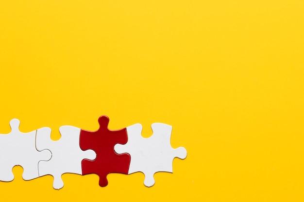 Rotes und weißes puzzlespielstück mit gelbem kopienraumhintergrund