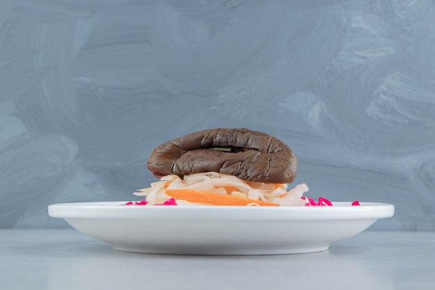 Rotes und weißes sauerkraut mit auberginen auf weißem teller.