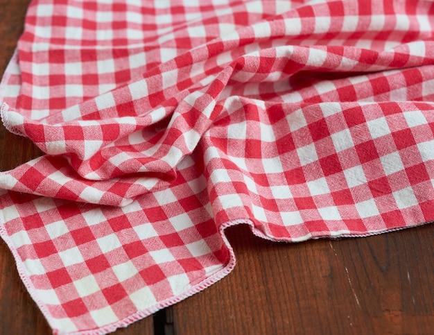 Rotes und weißes textilküchentuch auf einem braunen hölzernen hintergrund