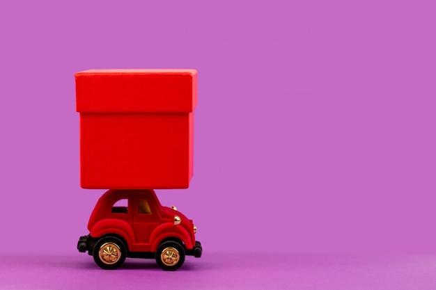 Rotes veloursspielzeugauto mit einer roten geschenkbox für weihnachten, neujahr, valentinstag, geburtstag auf einem hellpurpurnen mit copyspace