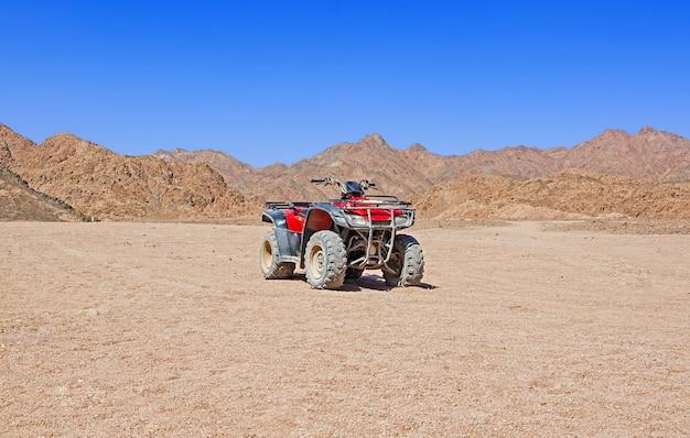 Rotes viererkabelfahrrad in der wüste