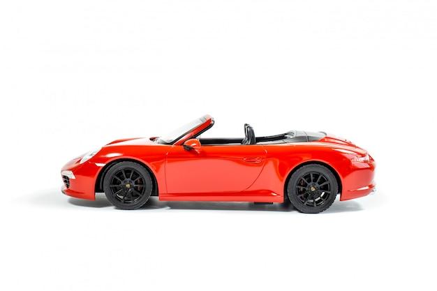 Rotes vorbildliches spielzeugauto lokalisiert auf weißem hintergrund. seitenansicht. weicher fokus.