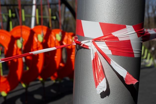 Rotes warnband auf dem kinderspielplatz, wegen covid-19-quarantäne geschlossen