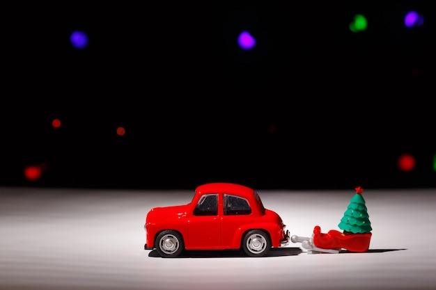 Rotes weihnachtsauto, das einen schlitten mit einem weihnachtsbaum am heiligabend trägt