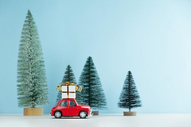 Rotes weihnachtsauto mit einer geschenkbox in einem kiefernwald. frohes neues jahr karte