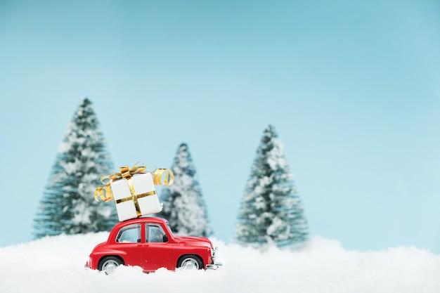 Rotes weihnachtsauto mit einer geschenkbox in einem verschneiten kiefernwald. frohes neues jahr karte