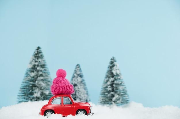Rotes weihnachtsauto mit gestricktem rosa hut in einem verschneiten kiefernwald. frohes neues jahr karte