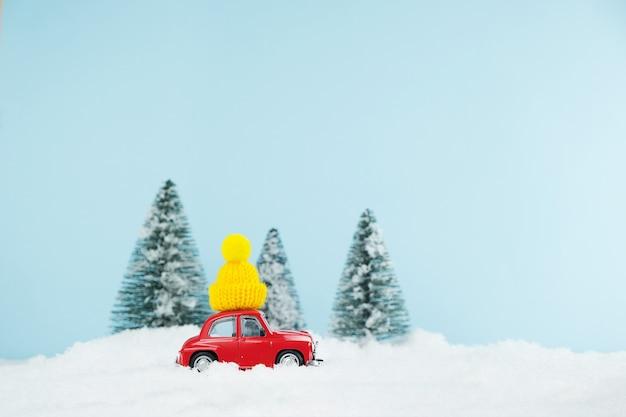 Rotes weihnachtsauto mit gestrickter gelber mütze in einem verschneiten kiefernwald. frohes neues jahr karte