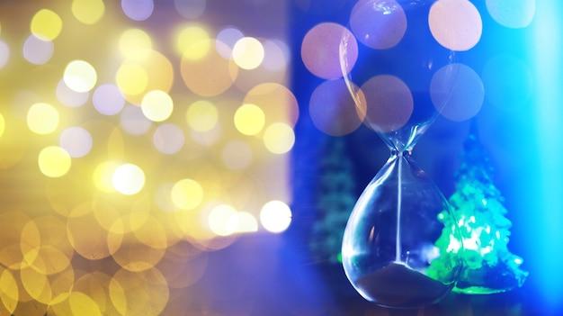Rotes weihnachtsbaumspielzeug auf einem ast eines natürlichen tannenbaums mit lichtern von girlanden in unschärfe im hintergrund. metallspielzeug mit schlitzen aus hirschen und schneeflocken. weihnachten, neues jahr, kopienraum, bokeh.
