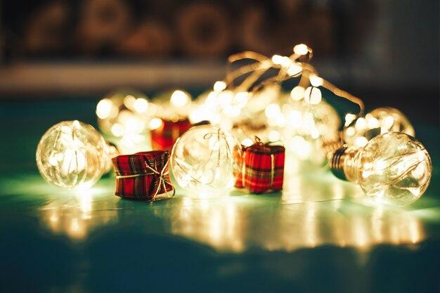 Rotes weihnachtsgeschenk mit exemplarplatz. weihnachtsbox mit lichterketten und dekorationen.