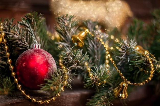 Rotes weihnachtsspielzeug unter den fichtenzweigen und den goldlichtern.