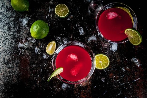 Rotes weltcocktail mit kalk im martini-glas auf dunklem rostigem hintergrund
