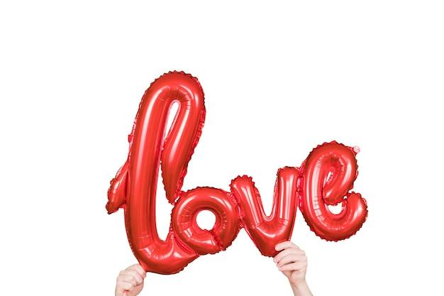 Rotgoldenes wort liebe aus aufblasbaren luftballons in händen. ballonbuchstaben der roten folie, konzept der romantik.