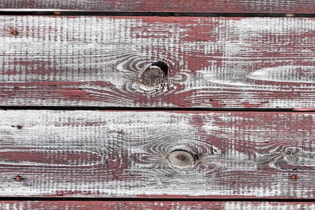 Rotgraue holzwand. horizontale bretter. alte farbe blättert ab. alte bretter. rotgraue holzstruktur einer abgenutzten bemalten tafel. rotgraue holzbeschaffenheit des alten abgenutzten bemalten brettes