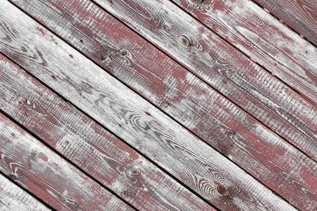 Rotgrauer hölzerner hintergrund. horizontale bretter. alte farbe blättert ab. alte bretter. rotgraue holzstruktur einer abgenutzten bemalten tafel. rotgraue holzbeschaffenheit des alten abgenutzten bemalten brettes
