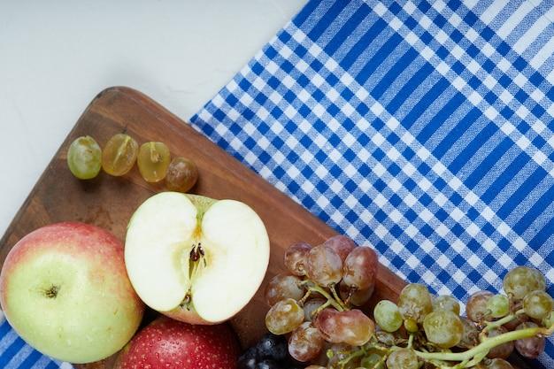 Rotgrüne äpfel und weintrauben auf einem holzbrett.