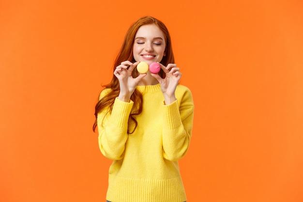 Rothaarige dumme und glückliche wunderschöne frau kaufen leckere makronen, halten essen und schauen mit verlangen