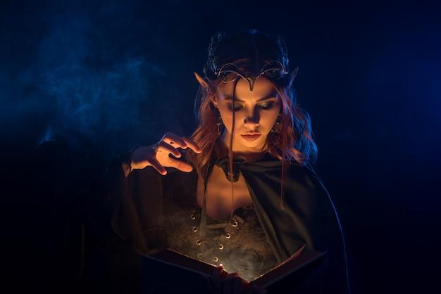 Rothaarige elfe in silberner tiara lernt zauber aus dem buch.