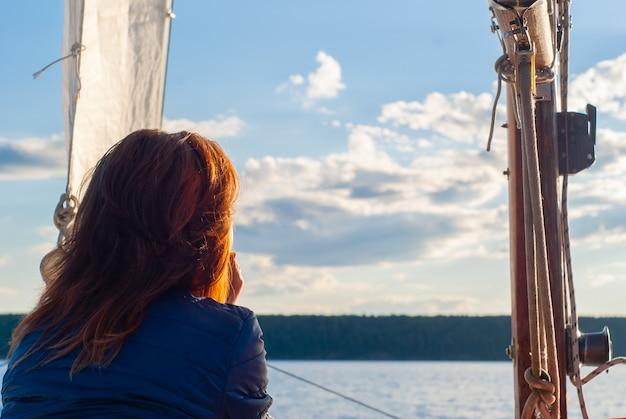 Rothaarige frau auf einem segelboot, die den sonnenuntergangshimmel und das ferne bewaldete ufer bewundert